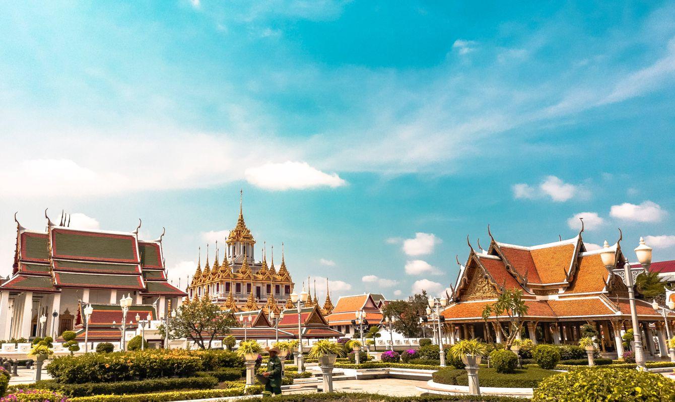 Bangkok temple building among green shrubs against a blue sky.
