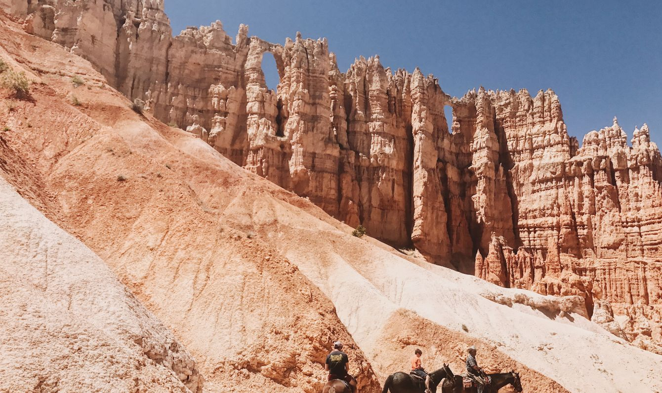 People riding on horses in a rocky landscape