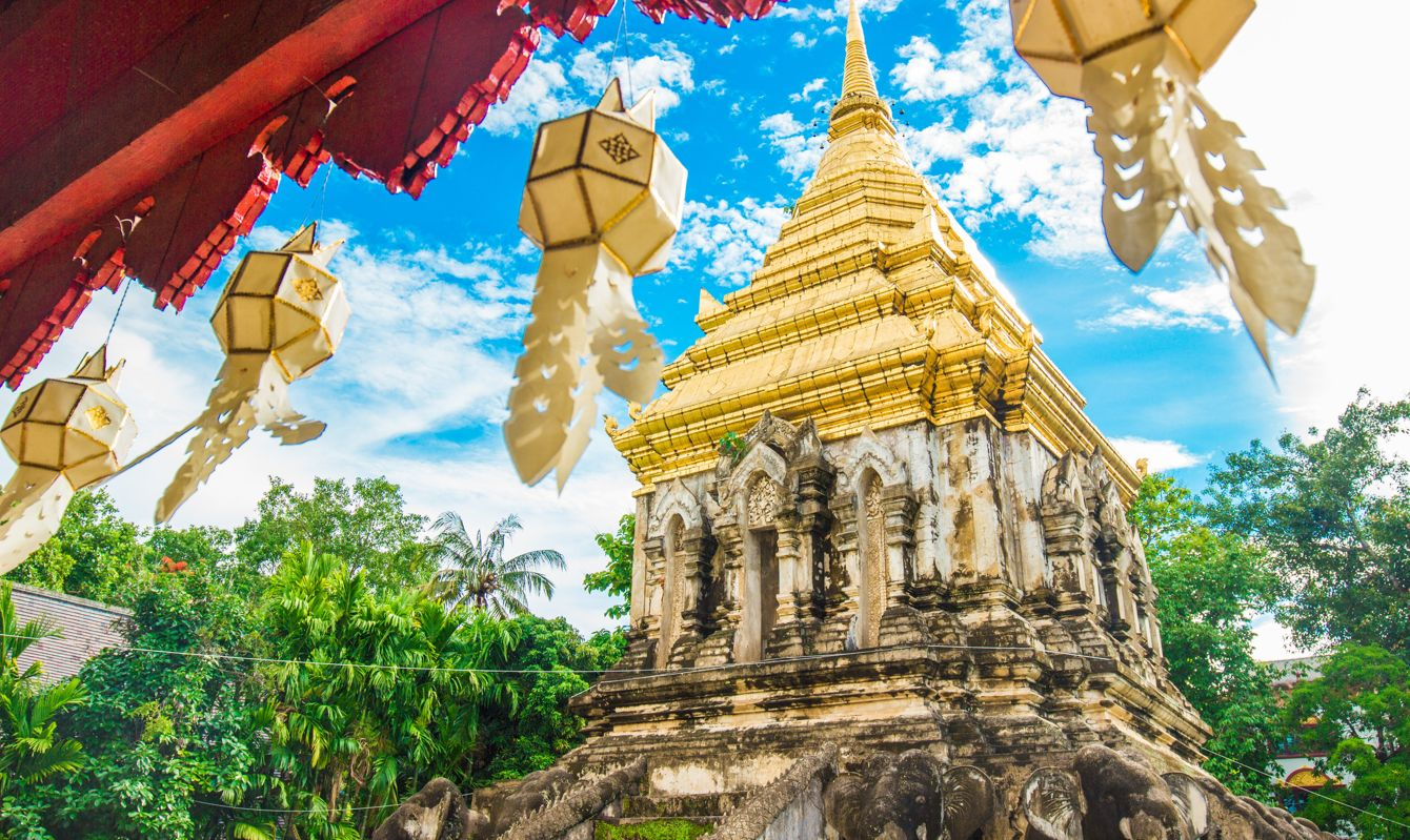 The golden roof of the Temple in Chiang Mai with hanging lanterns in the foreground.