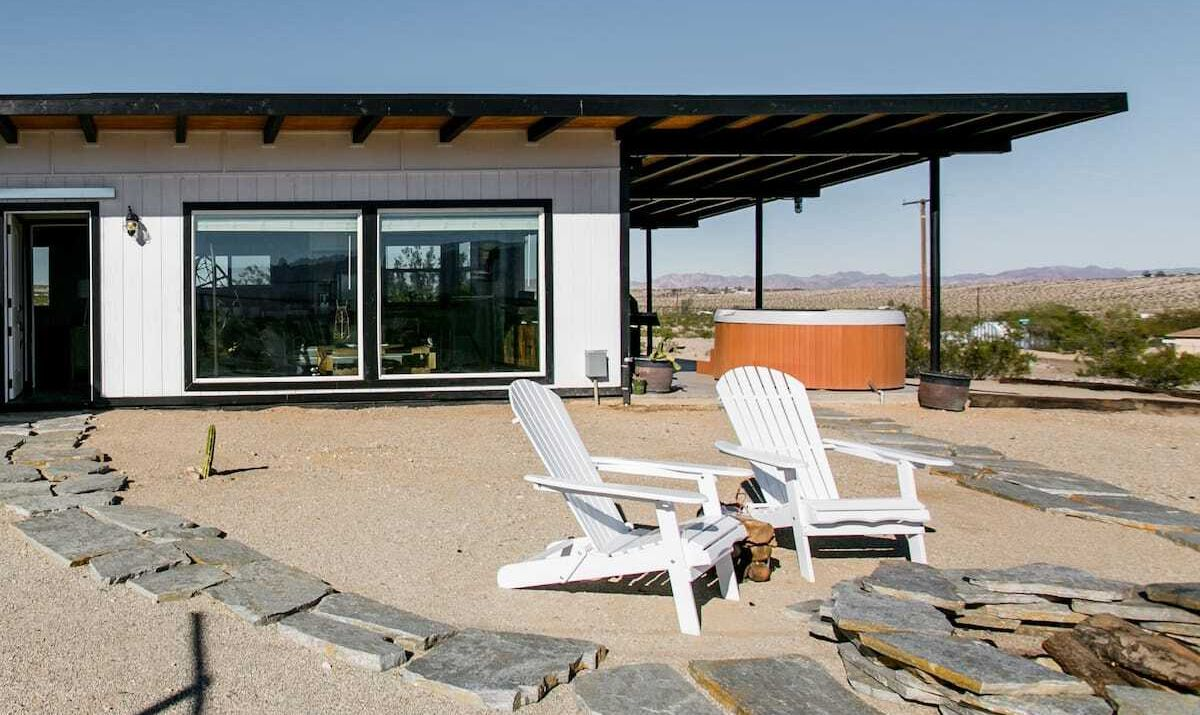 White wooden one-story house with flat roof and desert surroundings.
