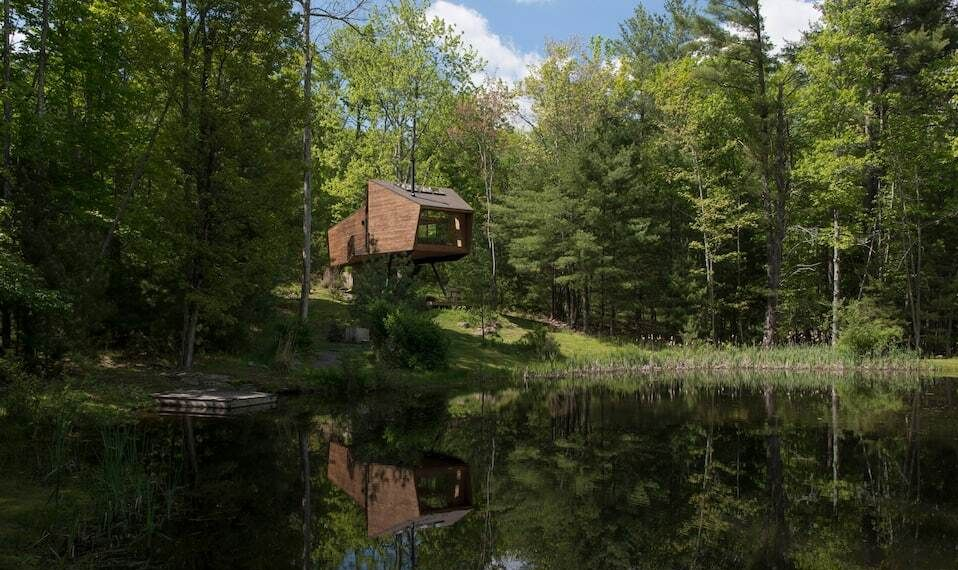 A geometric house on stilts overlooking a lake in forest surroundings.