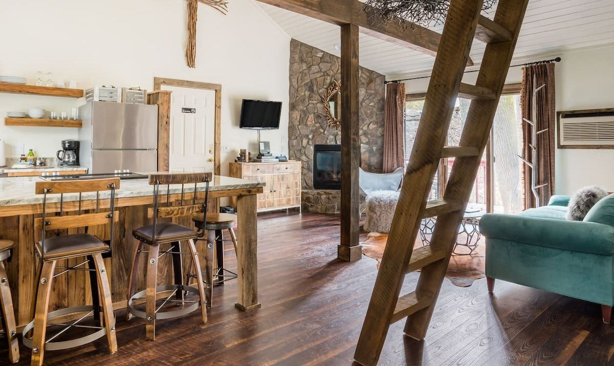 Rustic interior with a kitchen and a ladder up to the upper loft.
