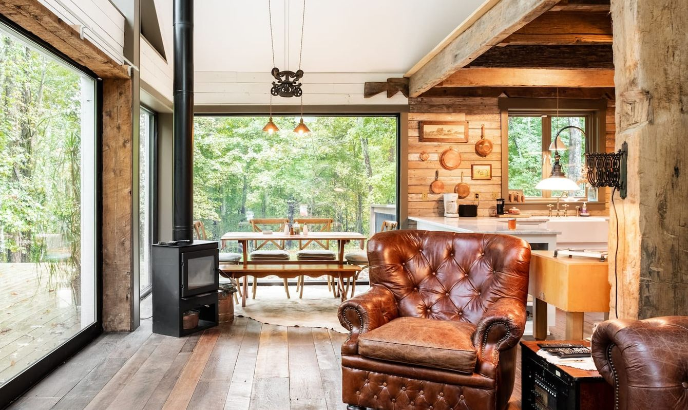 Airy wood cabin with large glass windows and a stove.