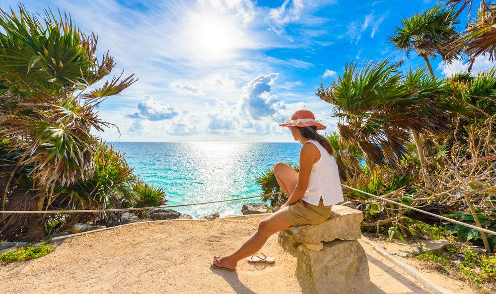 A young woman looking out over the ocean in Tulum, Mexico