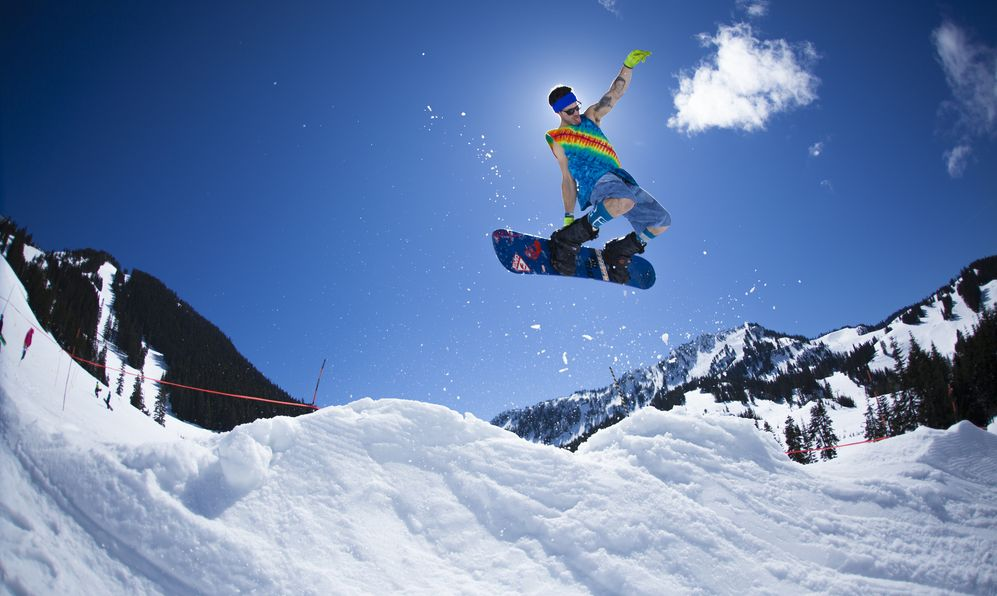 A Snowboarder grabs his board during a big air in the natural halfpipe competition at Stevens Pass during the Retro Fools Day Contest Festival