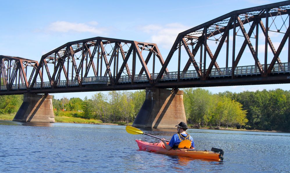a man kayaking by a bridge in Fredericton, New Brunswick, Canada