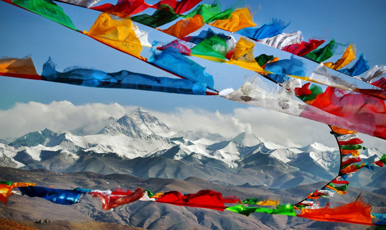 Mount Everest in Himalayas of Tibet viewed at distance through Buddhist prayer flags strewn across a high Himalayan Mountain pass Everest, known in Nepali as Sagarmatha and in Tibetan as Chomolungma, is Earth's highest mountain above sea level, located in the Mahalangur Himal sub-range of the Himalayas. The international border between Nepal and China runs across its summit point