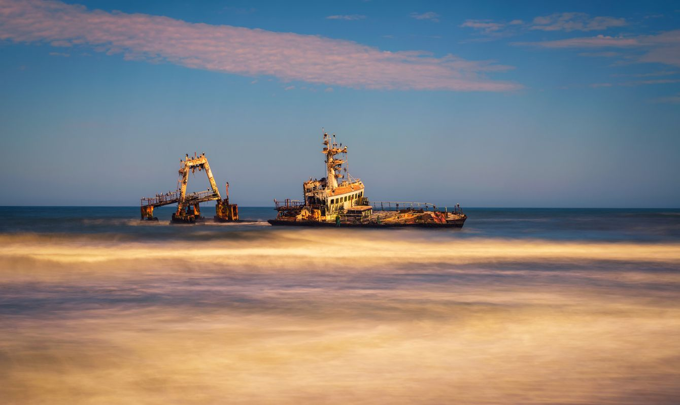 Abandoned shipwreck of the stranded Zeila vessel at the Skeleton Coast near Swakopmund in Namibia, Africa, with many cormorants sitting on the wreck. Long exposure.