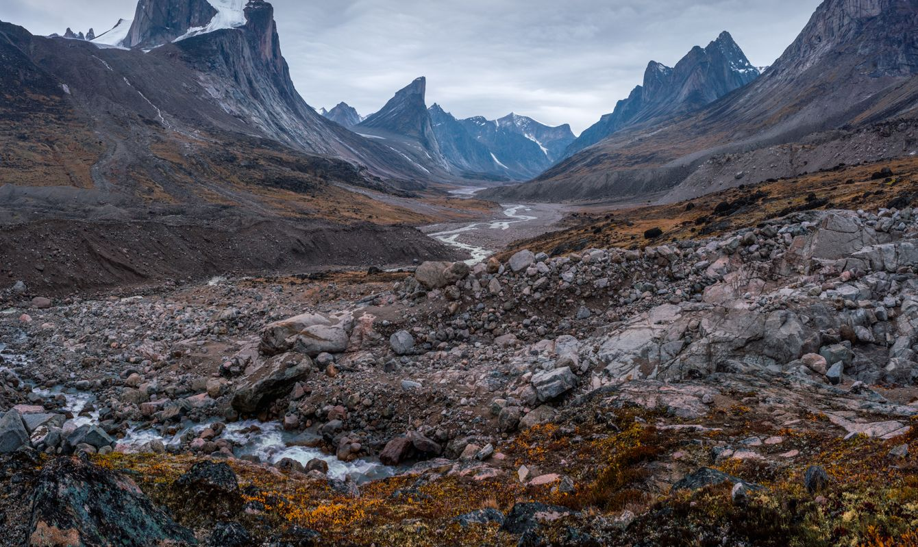 Wild Weasel river winds through remote arctic valley of Akshayuk Pass, Baffin Island, Canada on a cloudy day. Dramatic arctic landscape with Mt. Breidablik and Mt. Thor. Autumn colors in the arctic. Wild north.