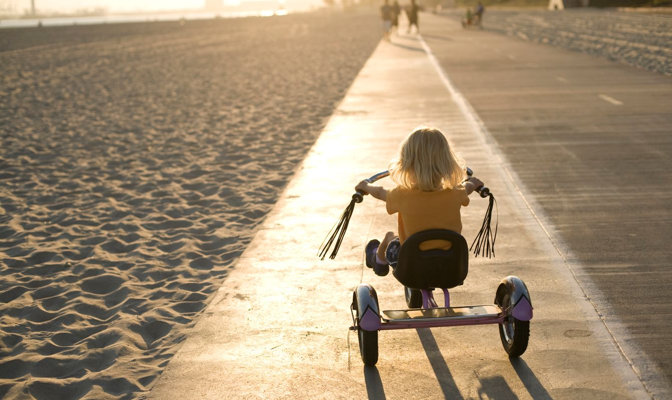 A young girl rides her tricycle towards the sunset on a bike path during a summer evening in Long Beach, Ca.
