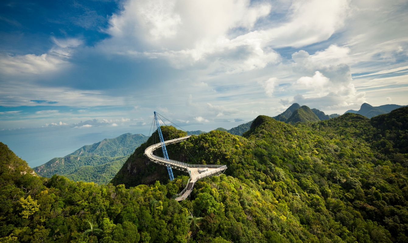 amazing cable bridge over the tropical rainforest island landscape in langkawi, malaysia.