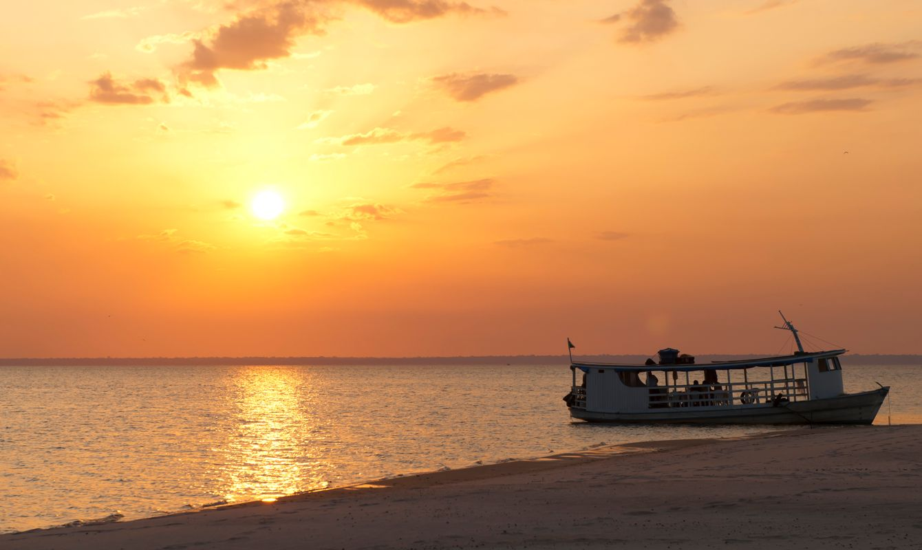 """Sunset over Tapajos river at Alter do ChA#o, a touristic beach near SantarAm, in the brazilian amazon."""