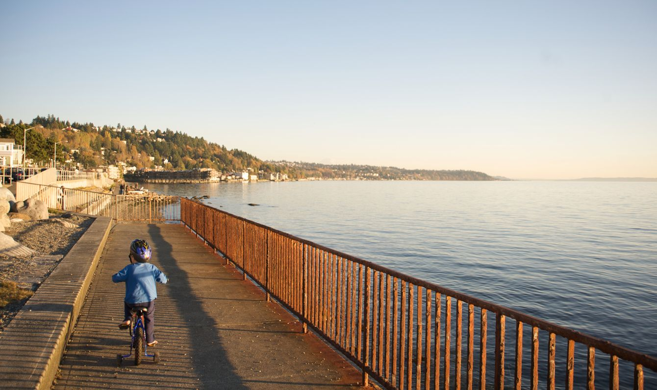 Boy rides bike with training wheels next to the Puget Sound in West Seattle.