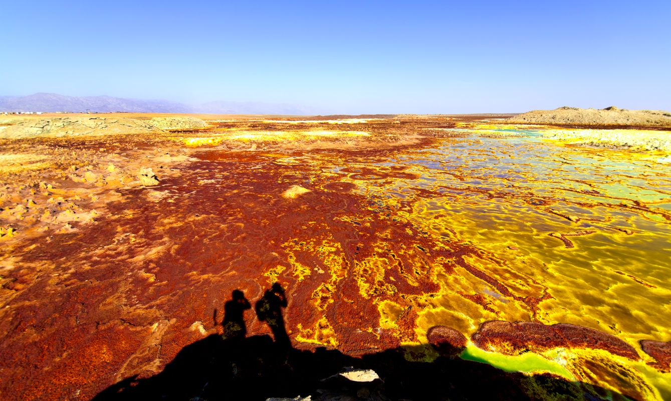 Two photographers at Volcanic remains after 1926 eruption as Hot Springs and geothermal / volcanic activity on Dallol Mountain. The characteristic white, yellow and red colours are the result of sulphur and potassium salts coloured by various ions. It is located in the Danakil Depression with the highest average temperatures on the planet and is considered the most remote and beautiful place on Earth, North East Ethiopia near Eritrea in Africa.