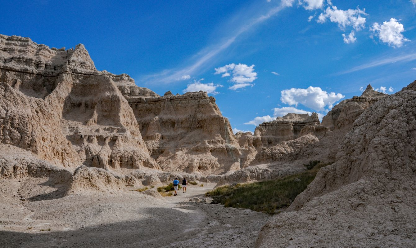 Hiking Notch Trail in the Badlands -- In Badlands National Park in South Dakota, two hikers delve deeper into the colorful formations of eroding rock.
