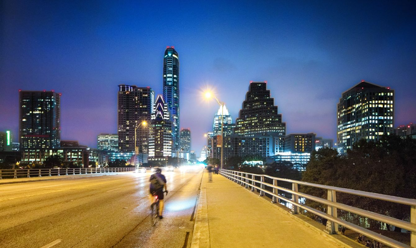 Austin panorama at night on Congess avenue bridge. A biker crosses at high speed while numerous tourists and locals are waiting for the bats to come out.