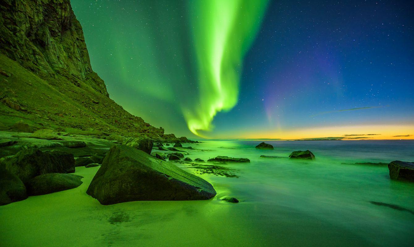 Uttakleiv beach in the Lofoten islands in Norway with strong green northern lights (Aurora Borealis)