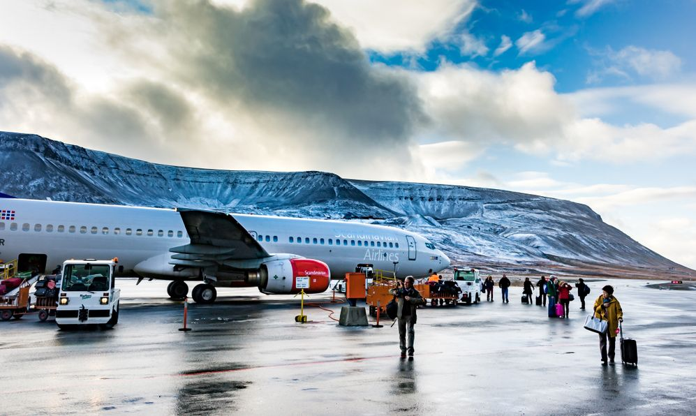 Arctic airport, airplane and passengers on a icy runway