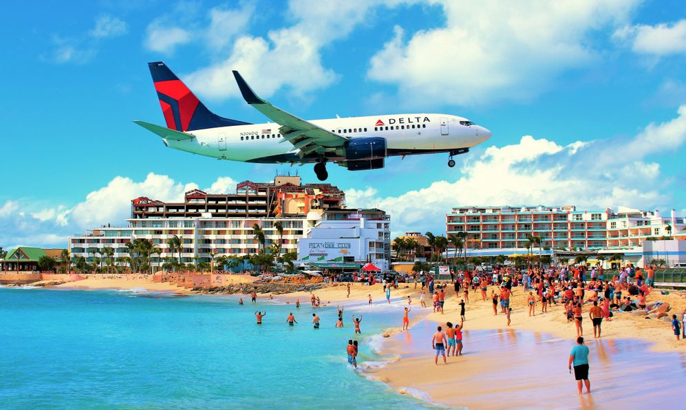 A Delta Air Lines plane flying low over the famous Maho beach as it comes in to land at Princess Juliana International Airport.