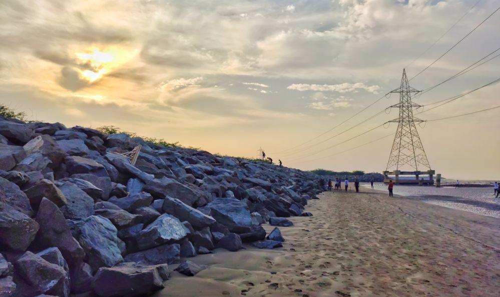 Sunrise at Dumas beach with power lines on the beach