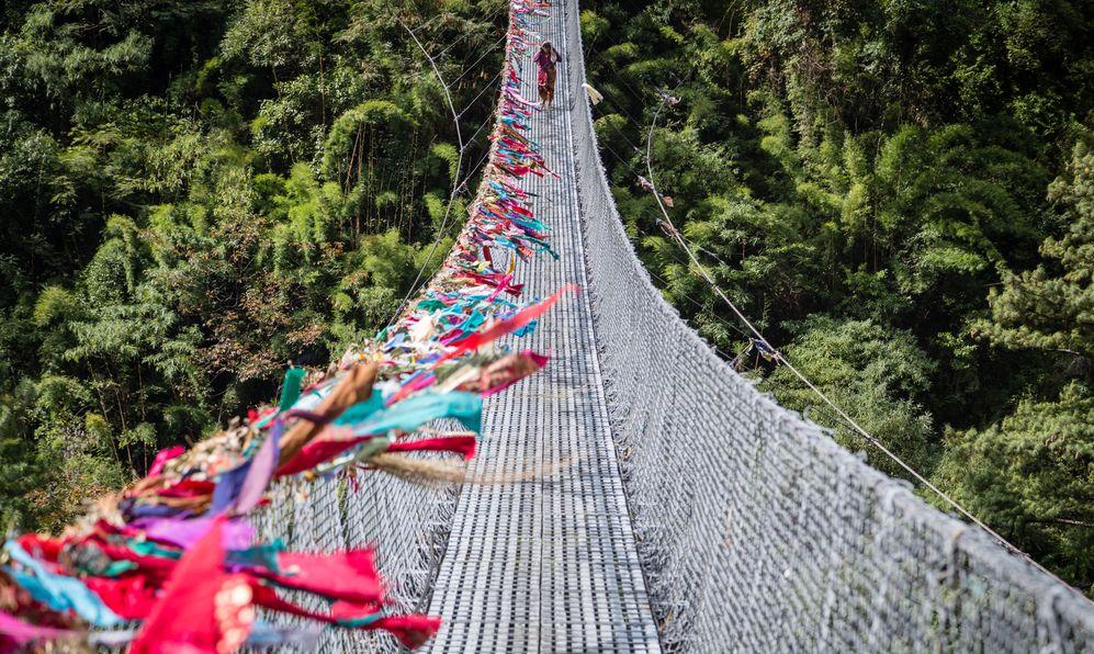Nepalese woman crossing a suspension bridge on the Annapurna Circuit.
