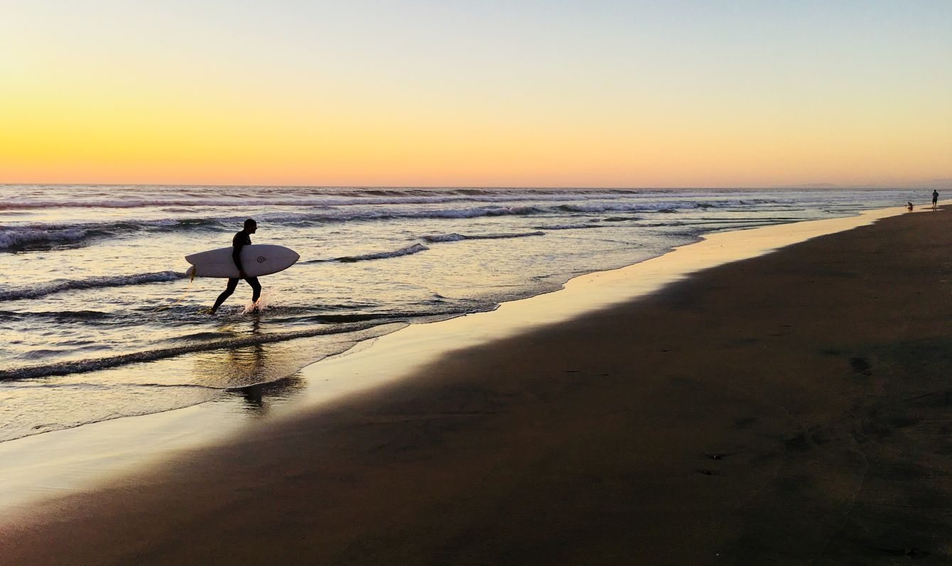 Surfer coming out of the water at La Jolla Shores