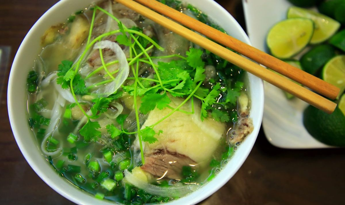 A bowl of Pho with vegetables.