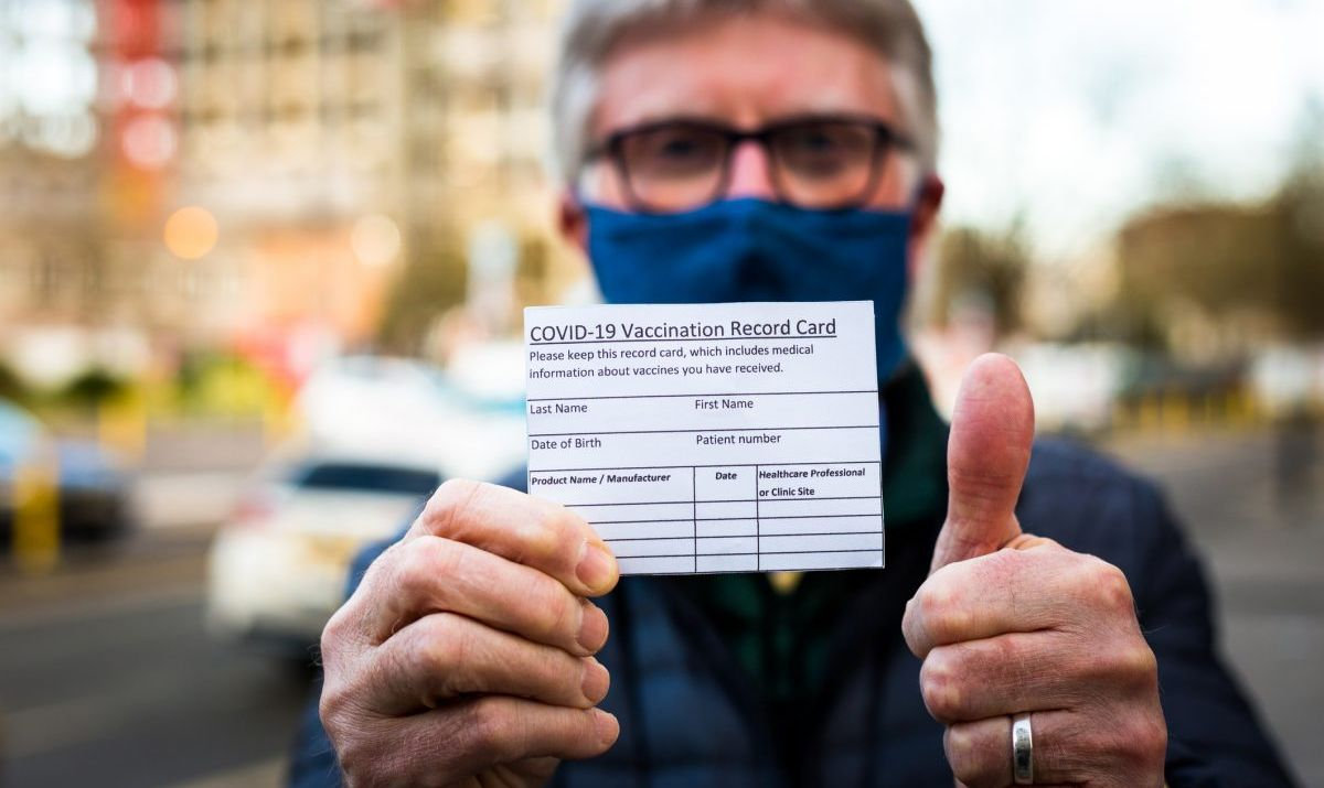 Man holding vaccination card