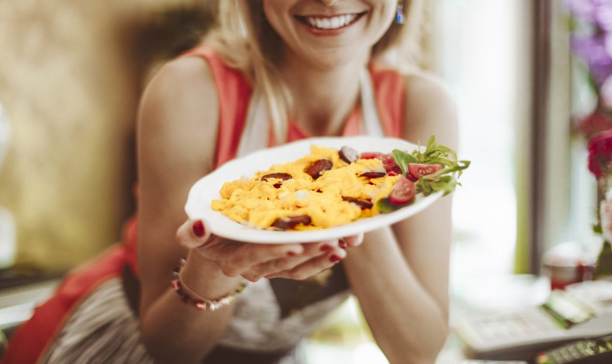 Woman showing a platter of scrambled eggs