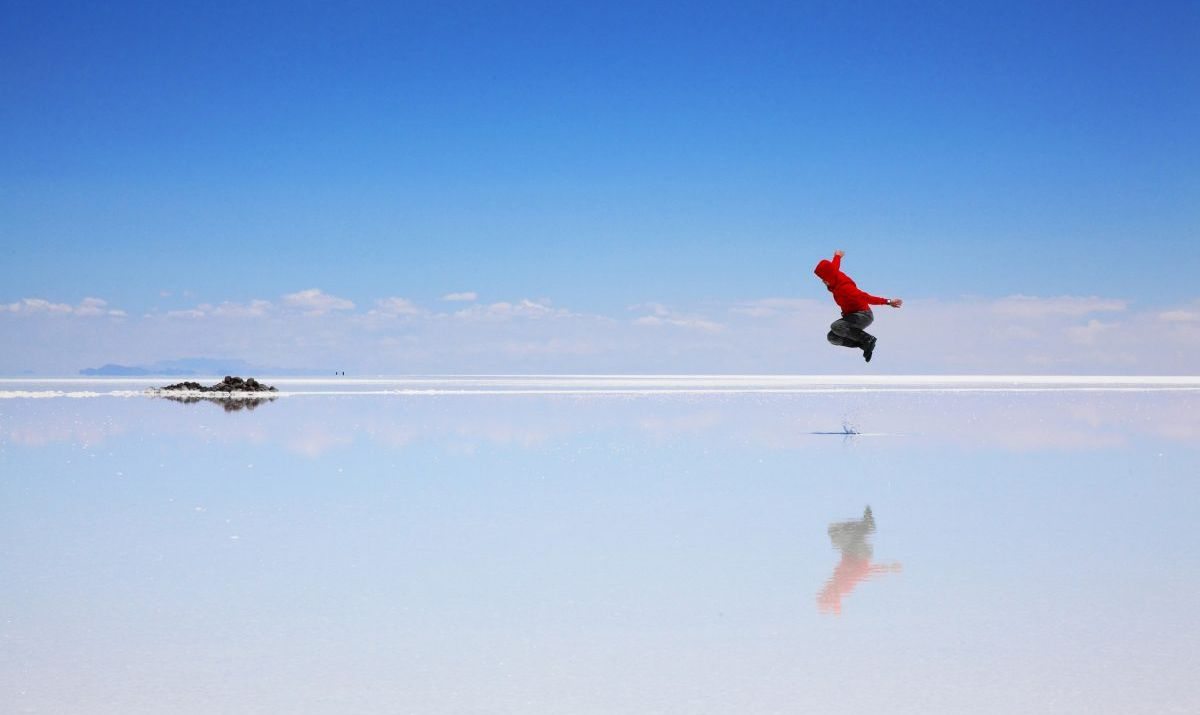Person jumping in Salar de Uyuni with the water reflecting the blue skies overhead