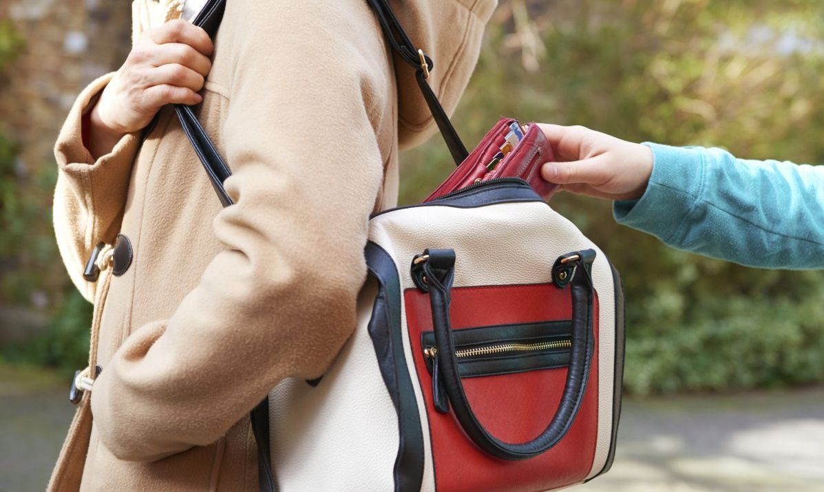 Pickpocket reaching into purse
