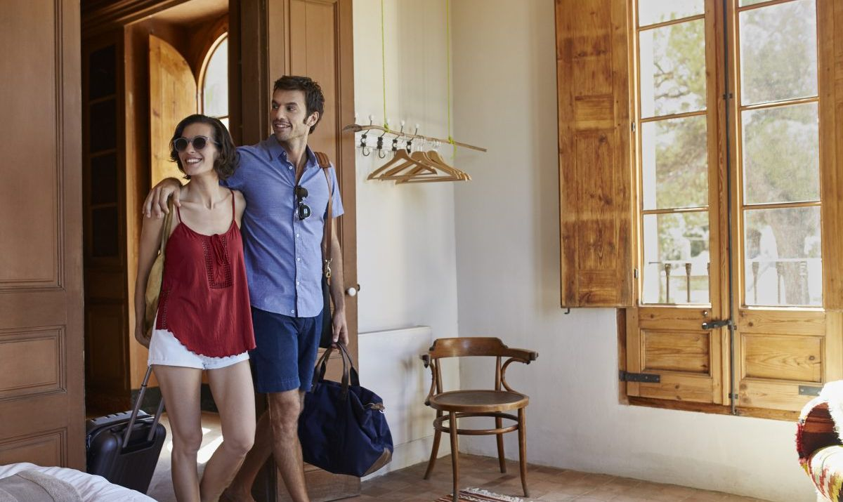 Couple with luggage entering hotel room