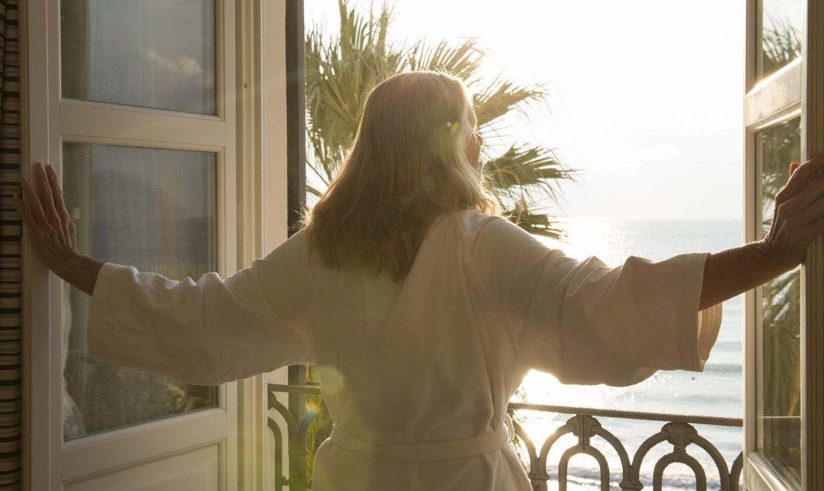 Woman in robe opening doors to her hotel room balcony.