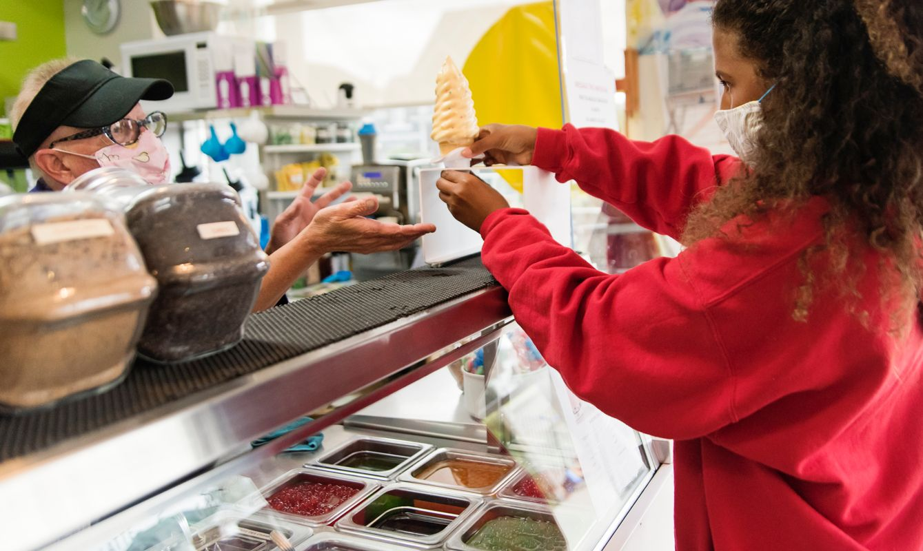 Mature women with cap, glasses and face mask serving customer in re-opened small ice cream parlour. Mixed-race teenage girl taking ice cream cone from a stand.