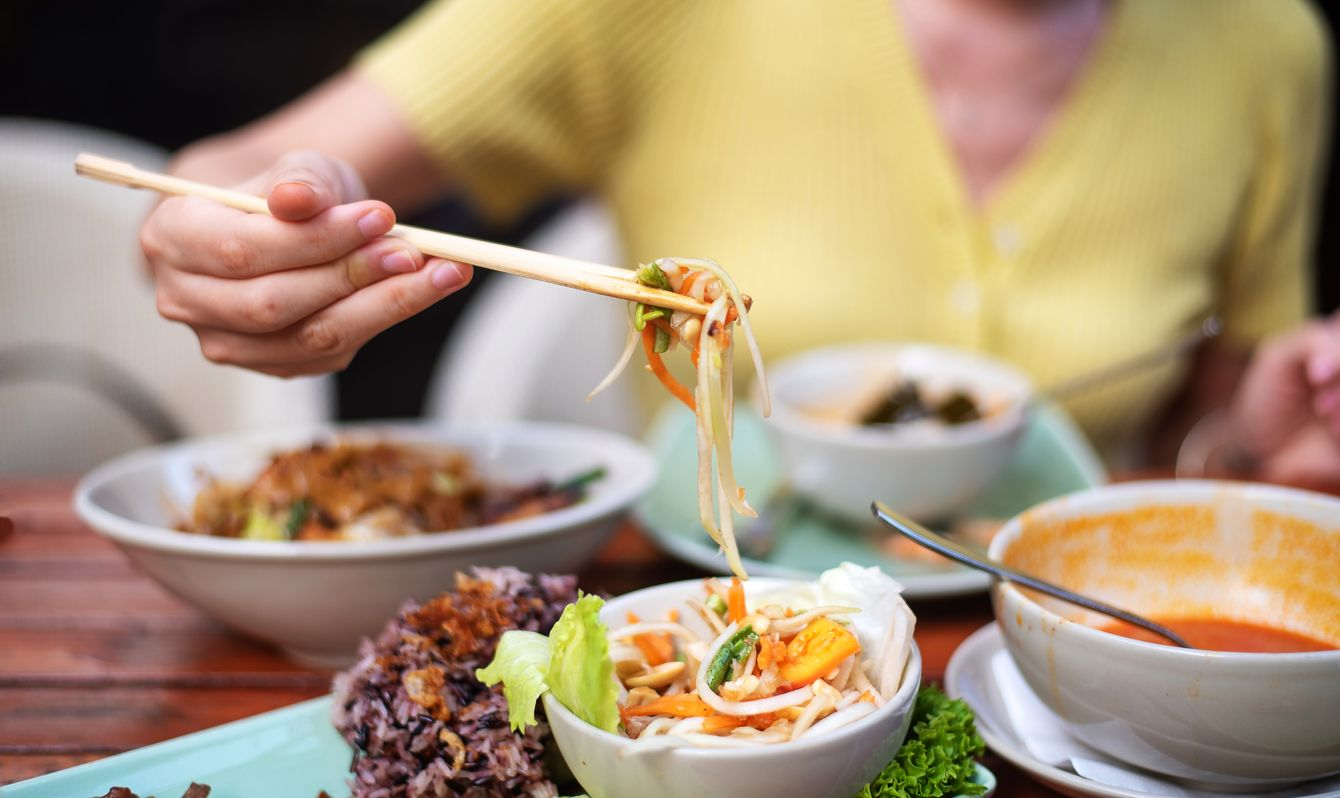 Woman having Som Tam green papaya salad classical Thai food of with BBQ chicken, sticky rice and raw salad vegetables on a wooden table background