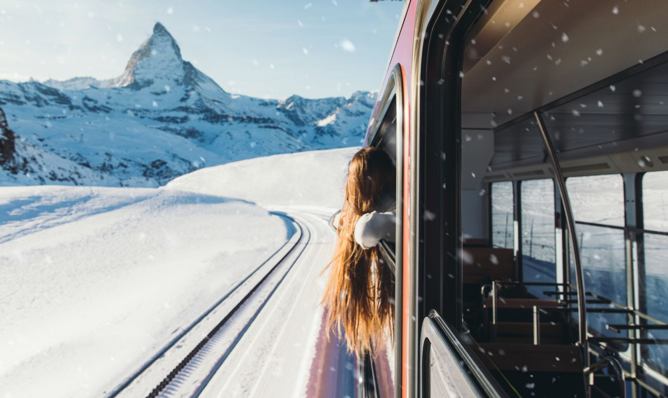Young woman with long hair enjoying the sunny winter day looking at Swiss Alps and Matterhorn mountains during the ride by the scenic train