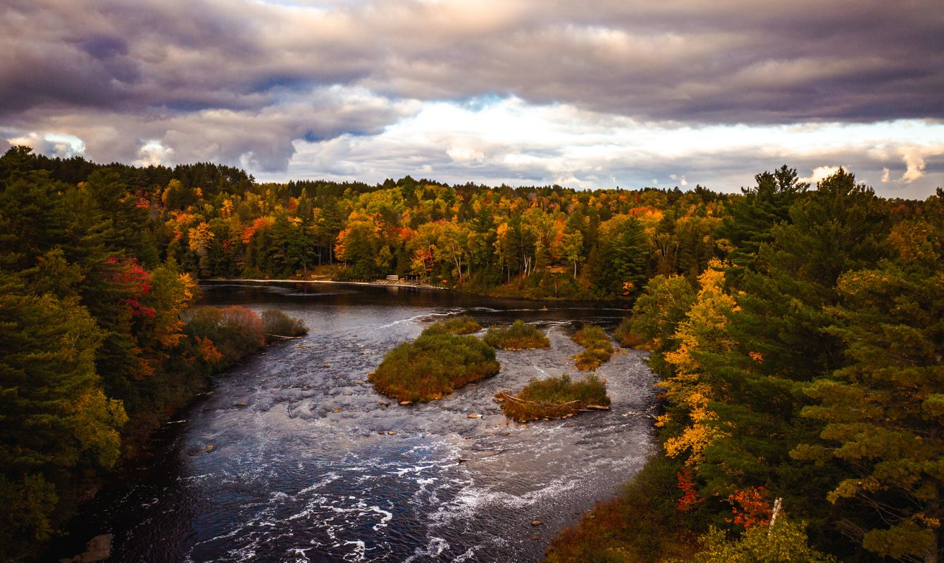 Beautiful aerial photograph looking down the Tahquamenon River lined with red, green, orange and yellow fall foliage colored trees with whitewater rapids and islands covered with vegetation.