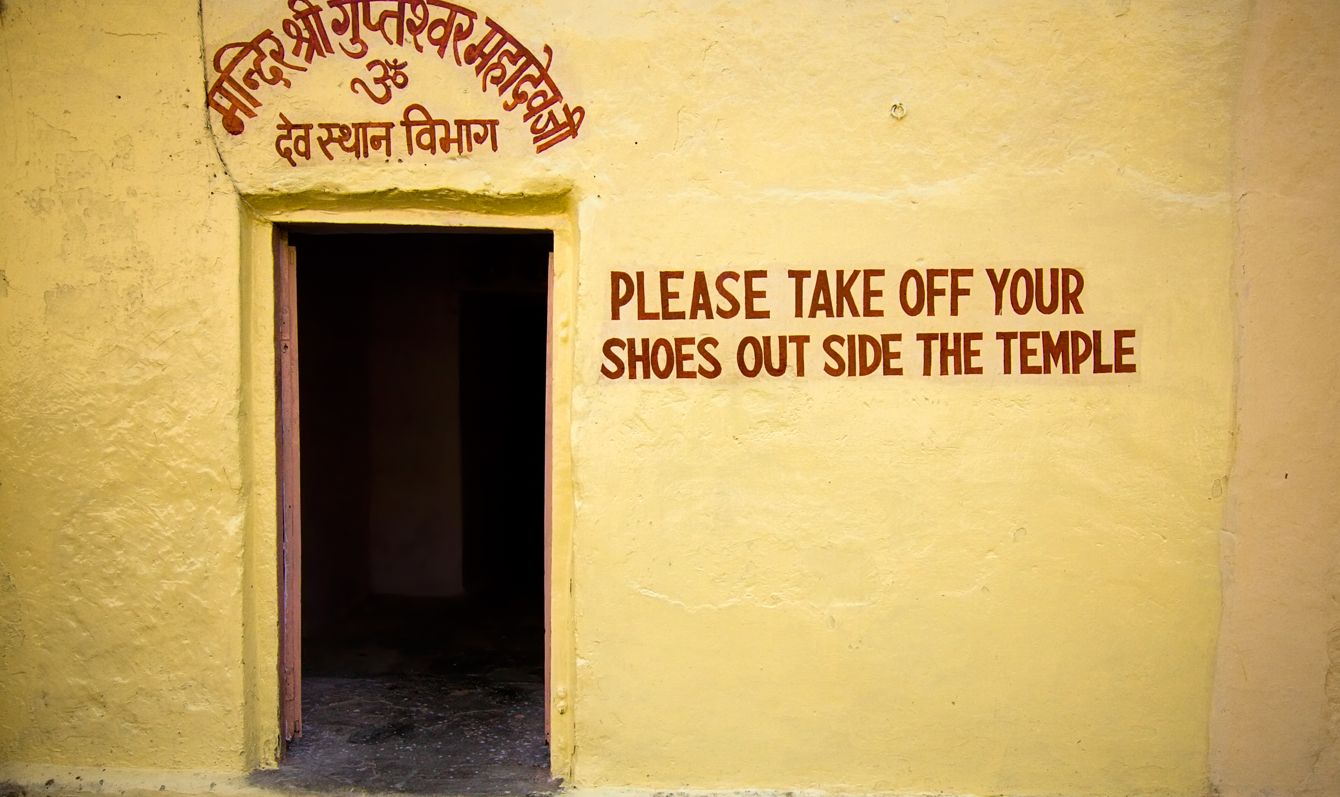 Writing on the wall of an indian temple asking to take shoes off - Jaipur, Rajasthan, India