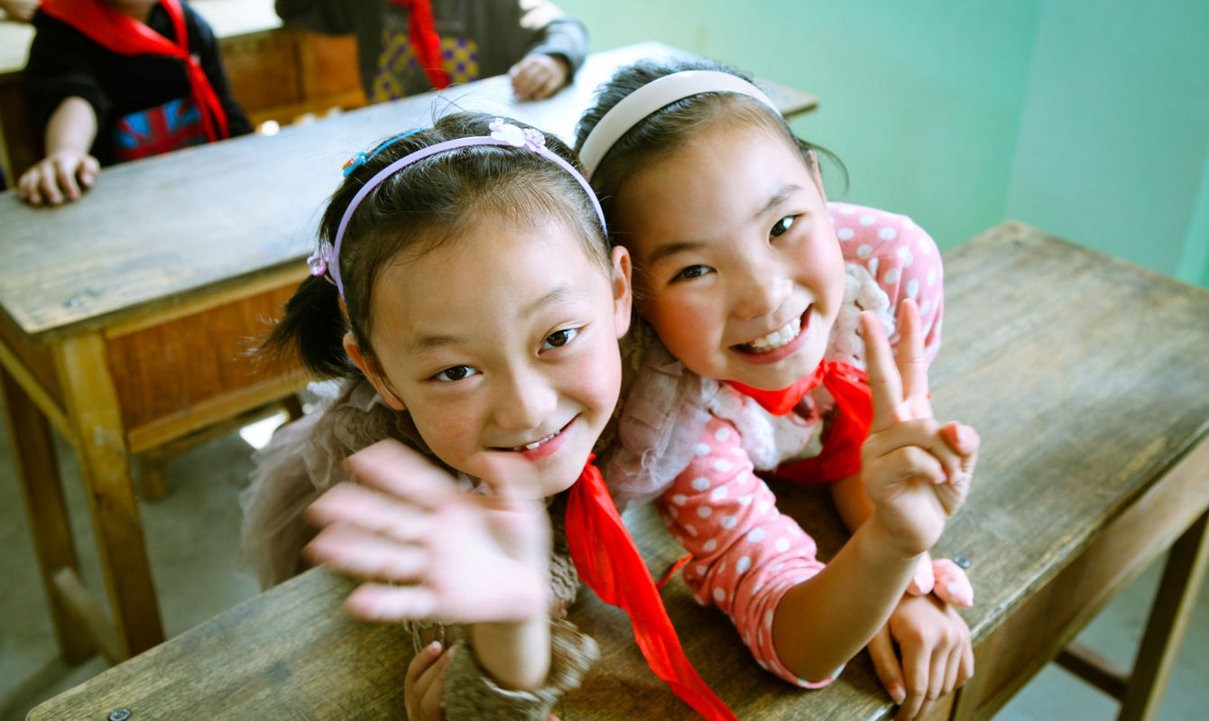Two Chinese elementary school students are shaking hand and posing victory sign to camera.