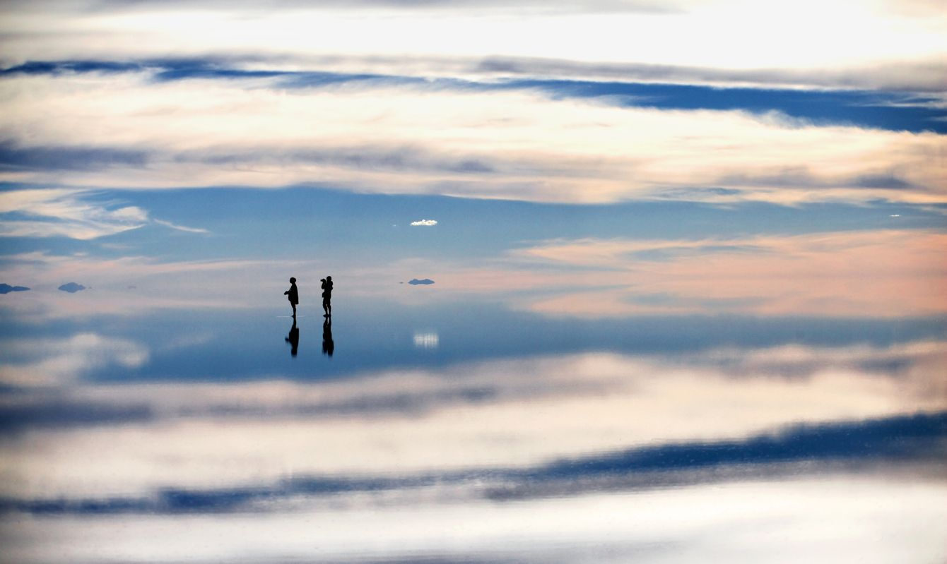 Two tourist stand in shallow water at the Salar de Uyuni, Bolivia