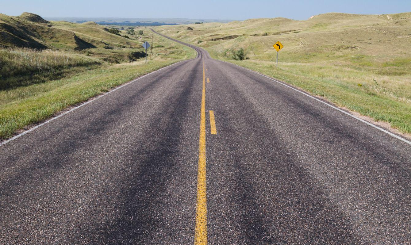 A blacktop highway in the sand hills of Nebraska.
