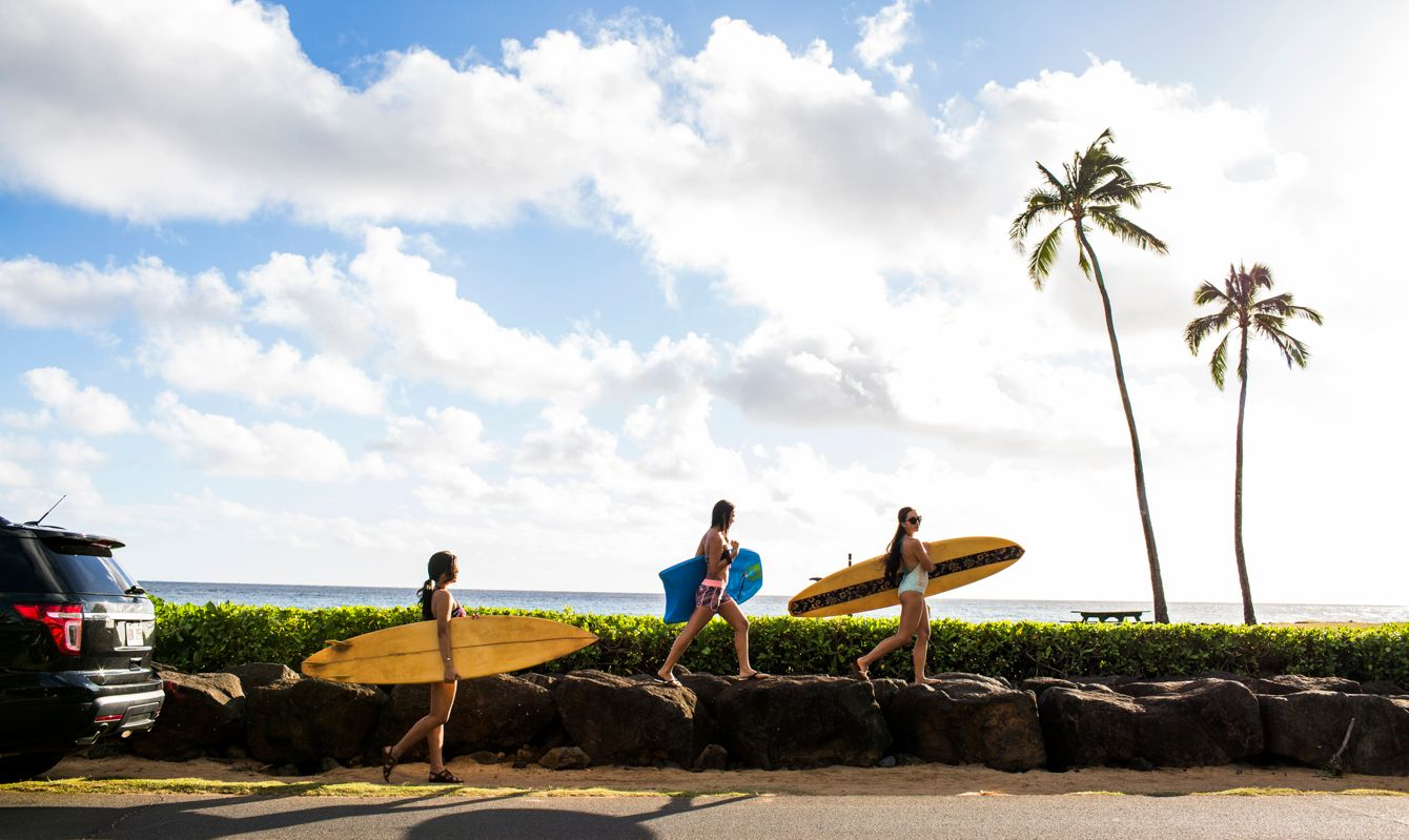Pacific Islander surfers carrying surfboards on rock wall