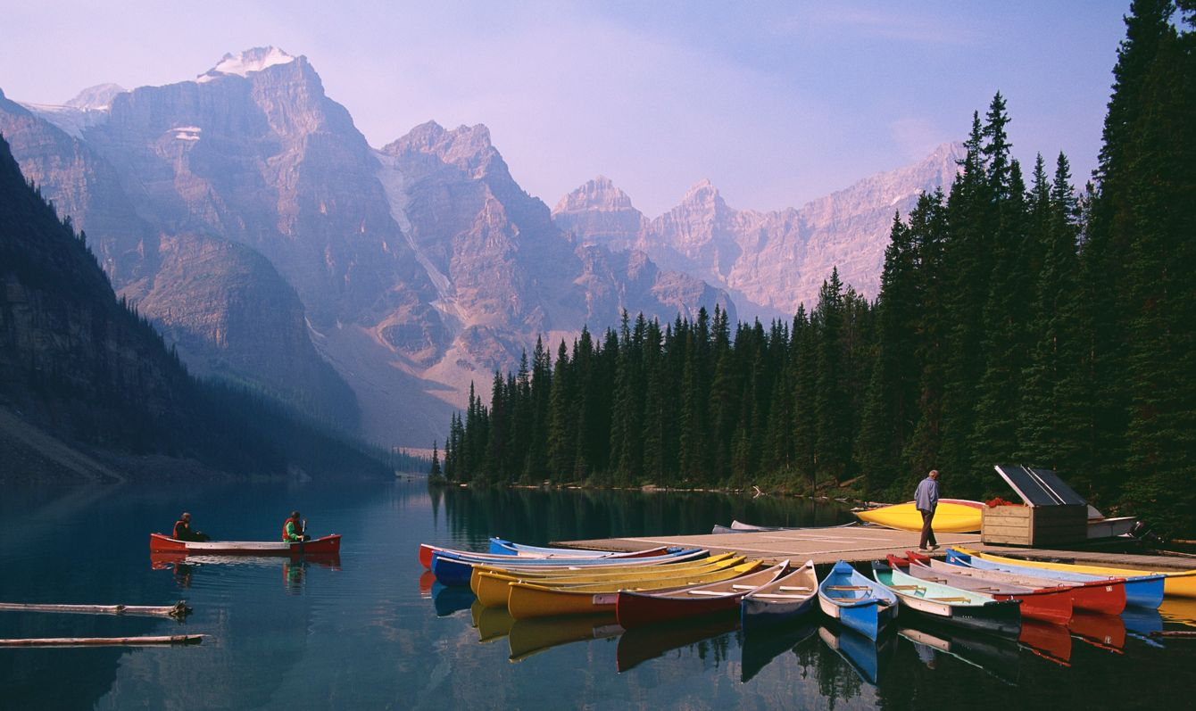 Canoeists paddle their canoe near a dock on Morraine Lake near Lake Louise in Banff National Park, Canada. | Location: near Lake Louise, Alberta, Canada.