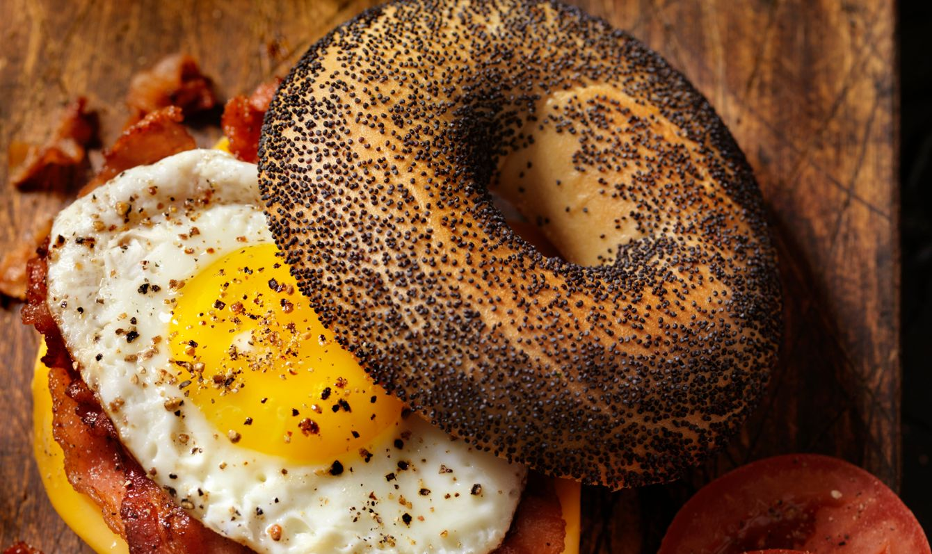 Poppyseed Bagel Sandwich with A Fried Egg, Bacon, Cheese and Tomatoes