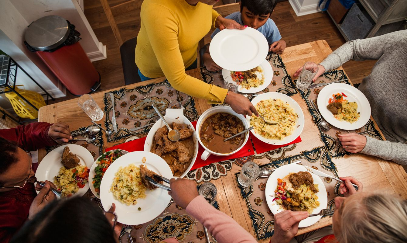 A woman serves a pilau rice dish to her family.