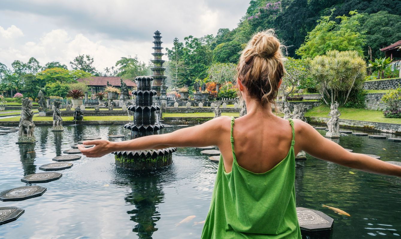 Young travel woman embracing the Royal water garden on sunny day in Tirtagangga, Bali Beautiful Tirta Gangga temple or water temple, Bali, Indonesia People travel Asia concept