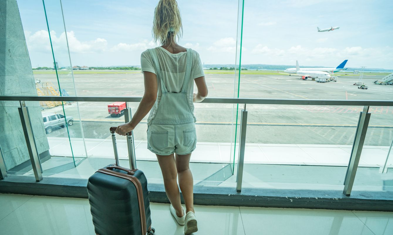 Young woman traveling at the airport standing by the window to look at airplanes. People travel dreaming vacations concept