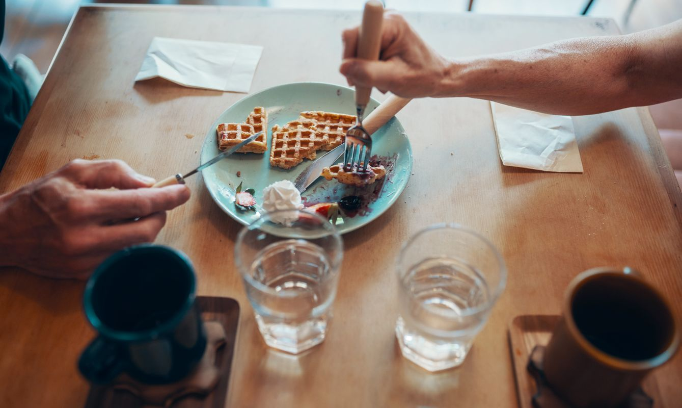 Close up of hands of a senior couple sharing a plate of waffles at a cafe
