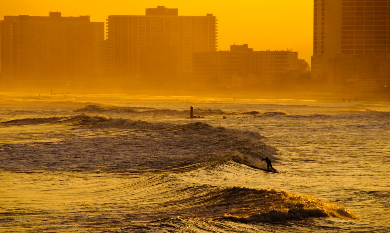 A surfer catches the last waves of the day as the sun is setting. Atlantic City, NJ