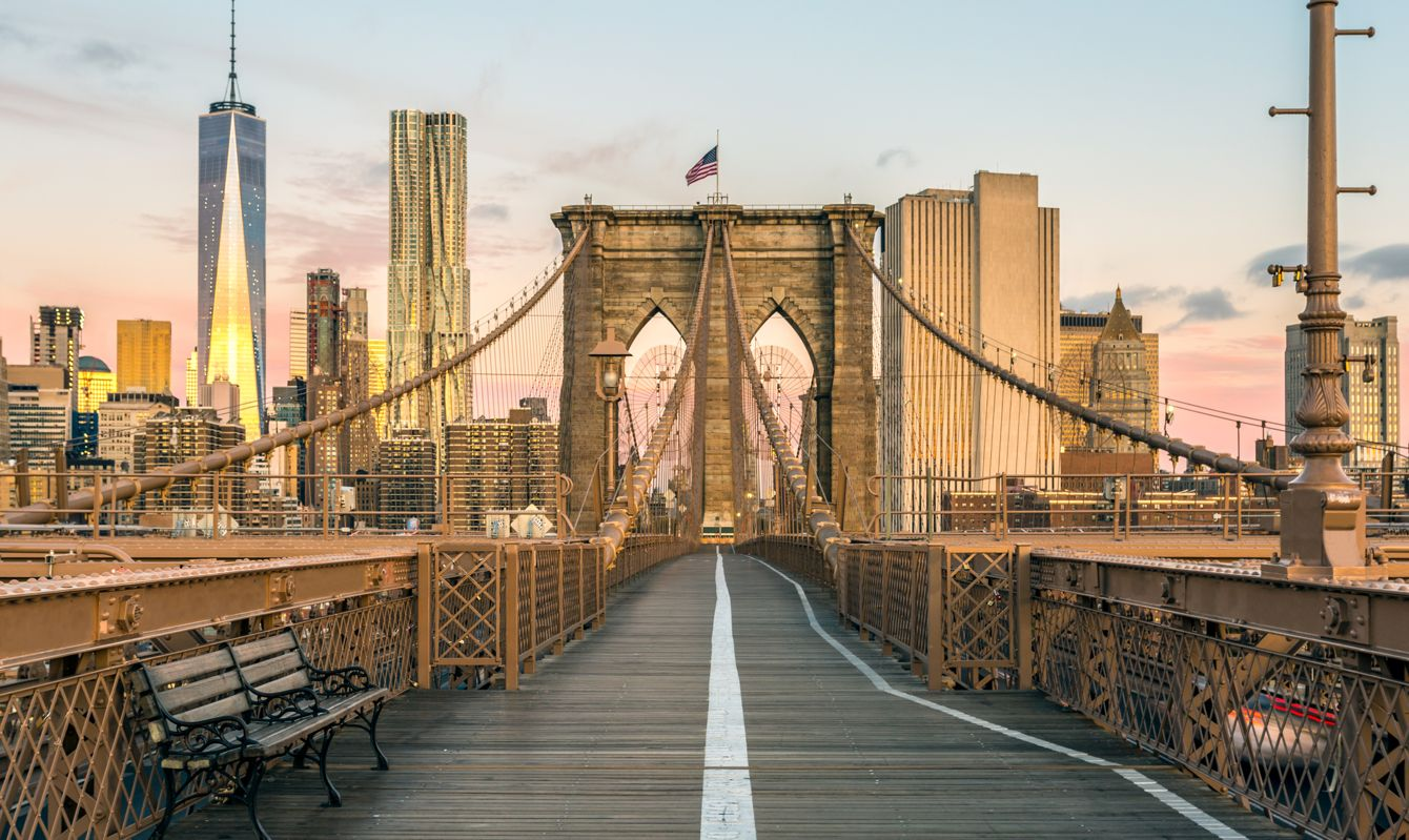 The Famous Brooklyn Bridge at Sunrise, New York City, USA. The sun is rising over Brooklyn on this beautiful day of Autumn